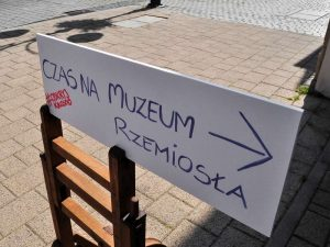 Drogowskaz kierujący zwiedzających do muzeum z napisem: czas na muzeum rzemiosła