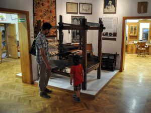 Zwiedzający na ekspozycji stałej w muzeum rzemiosła przy krośnie tkackim
