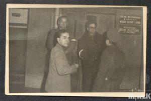Fotografia czarno-biała, grupa mężczyzn przed Domem Kultury