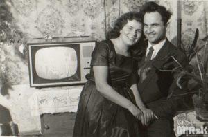 Fotografia biało-czarna. Młode małżeństwo pozuje przed telewizorem