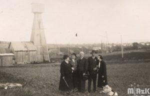 Widok na szyby naftowe, fotografia bialo czarna. Na pierwszym planie stoi grupa ludzi