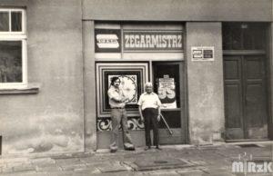Witryna zakładu zegarmistrzowskiego. Na pierwszym planie dwoch mężczyzn. Fotografia biało-czarna