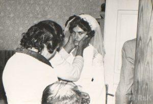 Przyjęcie weselne w domu, fotografia czarno-biała. Na pierwszym planie panna młoda