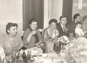Fotografia czarno-biała z przyjęcia weselnego. Przy stole siedzi kilka osób