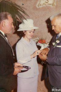 Fotografia kolorowa wykonana w urzędzie stanu cywilnego. Od lewej urzędnik oraz młoda para