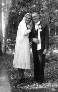 Fotografia biało czarna, na pierwszym planie stoi uśmiechnięta młoda para