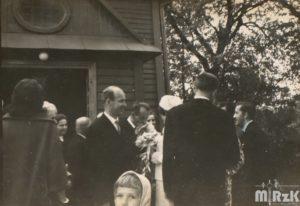 Grupa osób przed drewnianym kościołem składa życzenia młodej parze