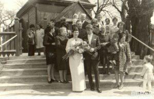 Fotografia zbiorowa na schodach do kościoła. Na pierwszym planie stoją państwo młodzi, za nimi goście
