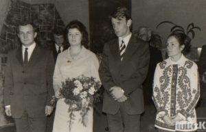Fotografia czarno-biała wykonana podczas ślubu cywilnego w urzędzie. Na środku stoją Państwo młodi, po bokach świadkowie