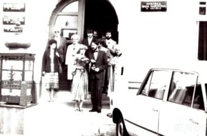 Młoda para wychodzi z urzędu stanu cywilnego, za nimi grupa osób. fotografia biało-czarna