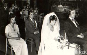 Fotografia biało-czarna wykonana w kościele. Na pierwszsym planie siedzą państwo młodzi, z tyłu świadkowie