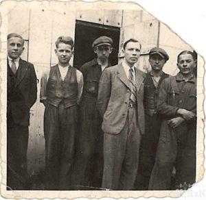 Grupa mężczyzn przed wejściem do warsztu