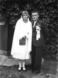 Fotografia biało czarna, na pierwszym planie stoi młoda para