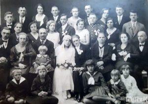 Fotografia biało-czarna, na pierwszym planie para młoda wraz z gośćmi