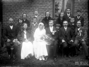 Fotografia ślubna, państwo młodzi a pierwszym planie, wokół nich goście