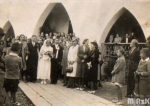 Orszak weselny przed budynkiem kościoła. Na pierwszym planie młoda para