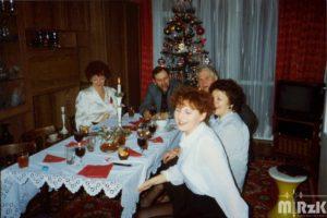 Fotografia kolorowa. W pokoju przy nakrytym stole siedzi 5 osób. W tle choinka