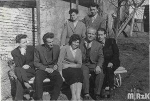 Fotografia czarno-biała. Kilka osób pozuje do zdjęcia siedząc na ławce przed budyniem