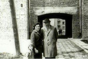 Mężczyzna, kobieta i dziecko pozują przed budynkiem z cegły