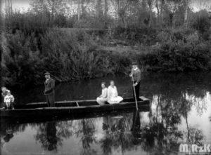 Widok na rzekę po której płynie łódź a na niej 4 osoby.