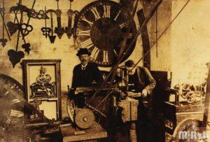 Dwóch mężczyzn przy pracy w fabryce zegarów. W tle dyża tarcza zegara wieżowego