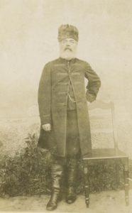 fotografia czarno-biała. Mężczyzna pozuje przy krześle, ubrany w długi płaszcz i czapkę