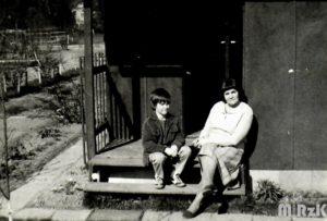 Kobieta i chłopiec siedzą na schodach domku działkowego