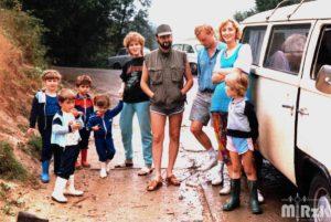 Rodzina z dziećmi stoi przy samochodzie.