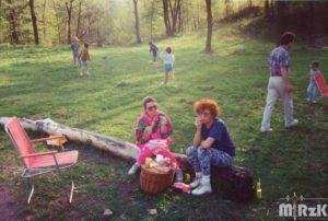 Na pierwszysm planie kobiety z koszem piknikowym, w tle bawiące się dzieci.
