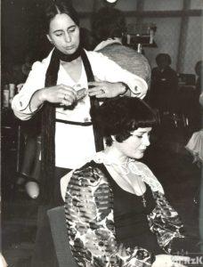 fotografia biało-czarna. Fryzjerka wykonuje fryzurę swojej klientce