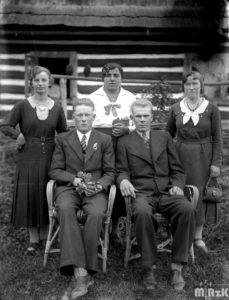 Pięć osób pozuje do zdjęcia przed przed drewnianym domem. Fotografia czarno-biała