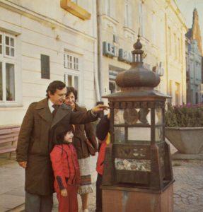 Rodzina wrzuca datki do skarbonki w kształcie wieży na krośnieńskim rynku.