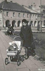 Kobieta z dzieckiem w wózku pozuje do zdjęcia na rynku w Krośnie