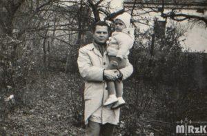 Mężczyzna z dzieckiem na rękach w ogrodzie. Zdjęcie czarno-białe.