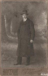 Fotografia czarno-biała, na środku mężczyzna ubrany w długi płaszcz