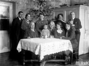 Fotografia czarno-biała. Za stołem pozuje rodzina. Za nimi widoczna choinka.