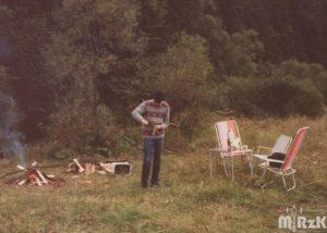 Fotografia kolorowa w plenerze. Na pierwszysm planie mężczyzna, dookoła biwak