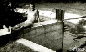 Mężczyzna opala się na betonowej tamie na rzece. Fotografia biało-czarna.