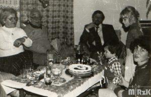 Przy zastawionym stole siedzi kilka osób. Kilkuletni chłopiec zdmuchuje świeczki z tortu.