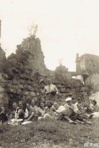 Grupa osób pozuje na ruinach zamku odrzykońskiego. Fotografia biało-czarna
