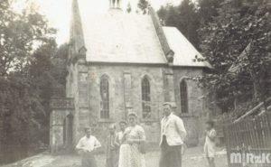 Czarno-biała fotografia. Kilka osób stoi przed Pustelnią św. Jana z Dukli