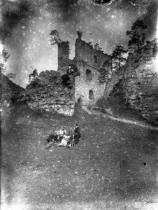 Stara czarno-biała fotografia. W centralnym miejscu, na trawie siedzi grupa osób. W tle zamek odrzykoński.