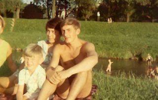 Fotografia kolorowa. Rodzina siedzi na kocu na trawie.