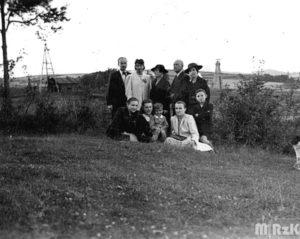 Grupa osób pozuje do zdjęcia na wzgórzu. W tle widać szyb naftowy.