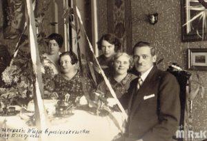 Grupa osób siedzi przy odświętnie nakrytym stole.