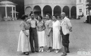 Fotografia czarno-biała. W tle pijalnia wód w Iwoniczu-Zdroju, na pierwszym planie stoi grupa osób