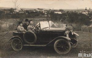 Fotografia biało-czarna. W starym samochodzie na wzgórzu siedzi 3 osoby. W tle widok na Krosno.