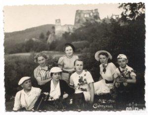 Grupa osób siedzi na trawie, w tle widać zamek odrzykoński