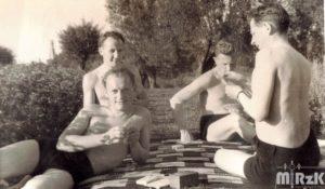 Fotografia biało-czarna. Czterech mężczyzna w strojach kąpielowych gra w karty na kocu