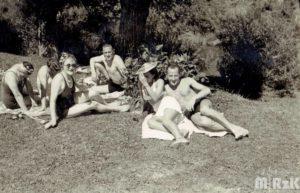 Fotografia biało-czarna. Sześć osób w strojach kąpielowych plażuje pod drzewem